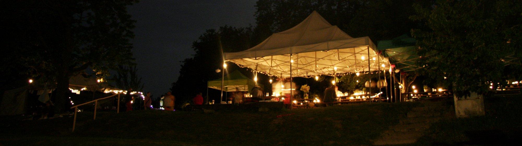 Večerní akce na zahradě s nasvíceným párty stanem